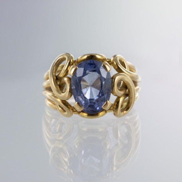 Bague pierre fine bleue avec brins entrelacés